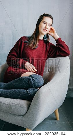 Young adult relaxed woman in casual outfit made of bordeaux sweater and kneesocks sitting in grey armchair in minimalist modern interior
