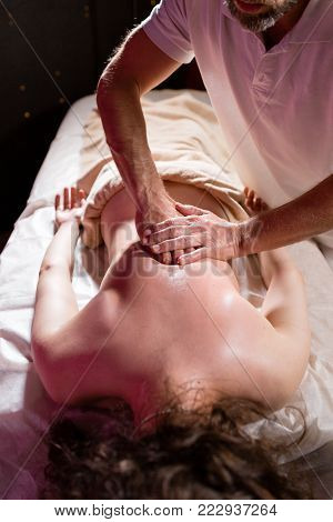 Masseur hands doing spine and back massage, neck and hand. Relaxed patient enjoys. Man hands massaging female. Spa centre concept. close-up.