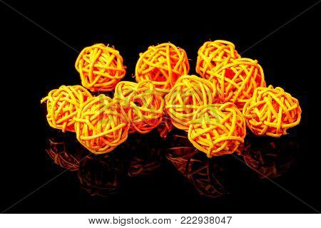 Orange rattan light balls on the black background. Creative decoration concept for Christmas celebration and Holiday.