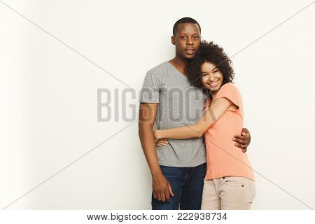 Happy african-american couple in casual embracing and smiling at white background, studio shot, copy space, isolated