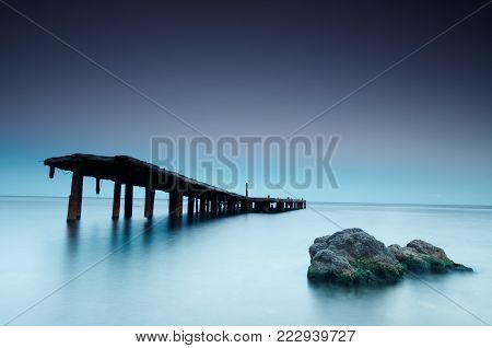 Old decaying and dilapidated pier with blur sea and rock