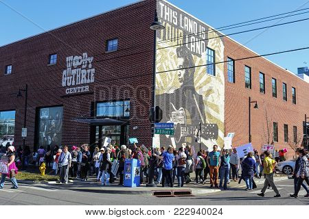 People gather by mural on that says This Machine Kills Fascists at Woody Guthrie Center at Womens March in Tulsa Oklahoma USA 1-2018