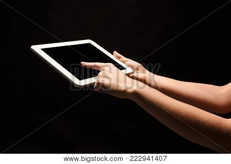 Female hands holding and pointing to blank screen of digital tablet. Caucasian woman using device with emty screen, copy space for advertisement, isolated on black background