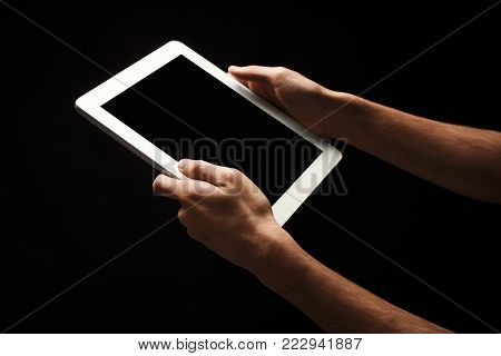 Male hands holding digital tablet with blank screen. Caucasian man using device with emty screen, copy space for advertisement, isolated on black background