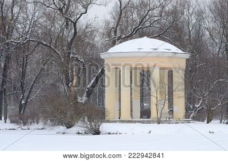 Yellow rotunda by the lake.Winter landscape with white snow.