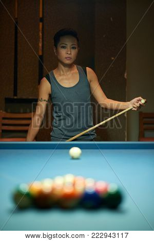 Female pool player thinking about her strategy for the game