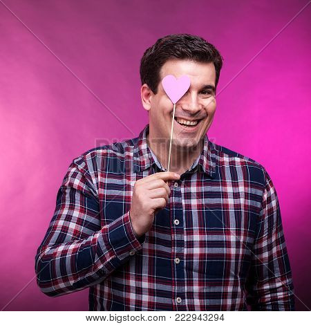 Funny adult man covering his right eye with a pink heart. Studio photo