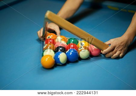 Player using triangle to rack up the billiard balls