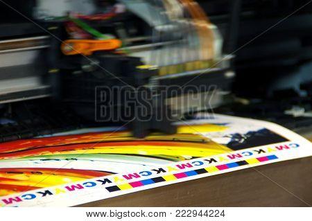 Inkjet printer plotter head moving over CMYK mark on white paper. Large digital printing machine.