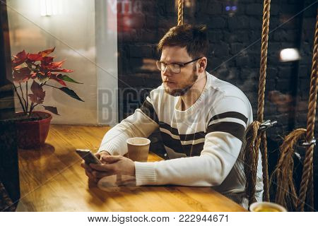 man drink tea in cafe and check his phone