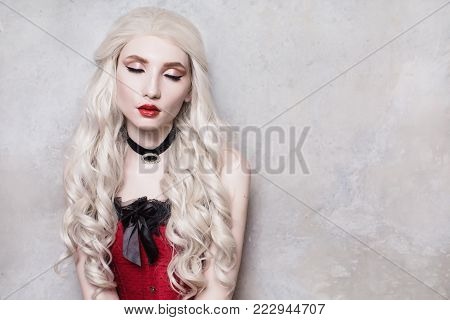 A model in stylish clothes. A stylish woman. Girl with a stylish hairstyle. Young stylish woman. Model in a stylish dress. Luxurious stylish blonde woman with beautiful long white hair and red lips on a gray background.
