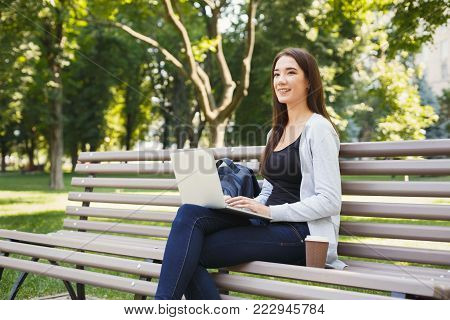 Smiling young woman working on laptop sitting on bench in park. Technology, communication, education and remote working concept, copy space