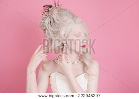 A blonde model with a beautiful luxurious rococo hair style in a white dress on a pink background. Young model on a gray background. Blonde model with a luxurious hairdo. Stylish model in retro dress. Model with natural make-up