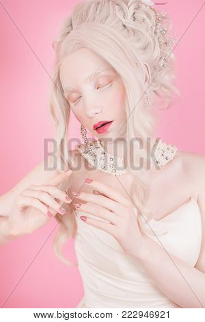 Fairy in retro dress. Beautiful fairy from a fairy tale. A young fairy with a beautiful hairdo. Fairy on a pink background. A blond fairy woman with a beautiful luxurious rococo hair style