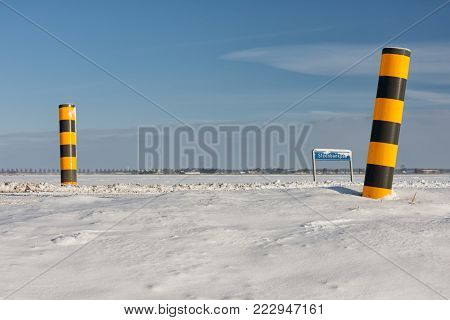 Dutch winter landscape with snowy farmland and colorful road signs to mark the country road
