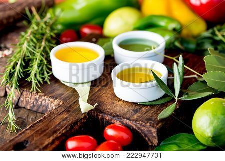 Oils, spices ahd herbs selection. Grape, olive and corn oils fresh herbs lemons, peppers.