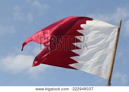 The national flag of Qatar, flying from a flagpole in Doha.