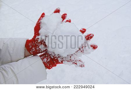 The hands dressed in red knitted woolen gloves hold a snow handful.