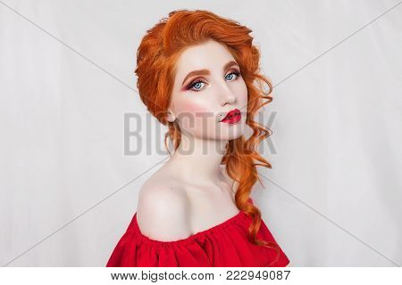 A model in stylish clothes. A stylish woman. Girl with a stylish hairstyle. Young stylish woman. Model in a stylish dress. Beautiful red-haired stylish girl in red dress posing on white background.