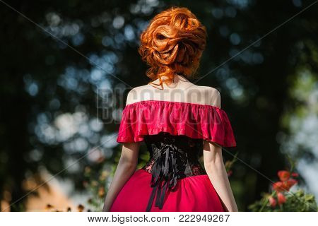 A model in stylish clothes. A stylish woman. Girl with a stylish hairstyle. Young stylish woman. Beautiful red-haired stylish girl in a red dress and in black stylish corset