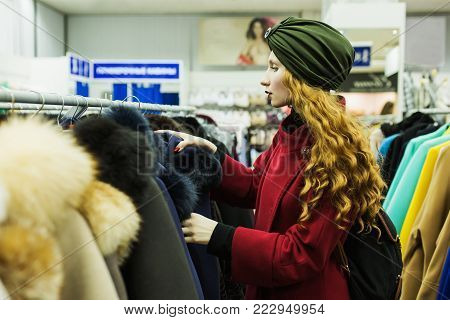 Red-haired girl with long hair chooses a winter coat in a store. The girl in the shop. Stylish woman in the shop. Make purchases in the big shop. Clothing shop. Shopping in a modern shop
