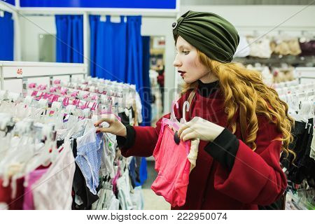 Red-haired girl with long hair picks underwear. The girl in the shop. Stylish woman in the shop. Make purchases in the big shop. Clothing shop. Shopping in a modern shop