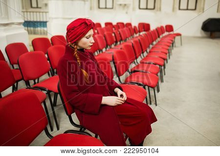 A girl in a red coat is sitting on a chair. A row of red chairs in the synagogue. A girl pray in a chair. A woman pray in a Jewish synagogue. The red-haired model pray in the old church. Woman pray to the god
