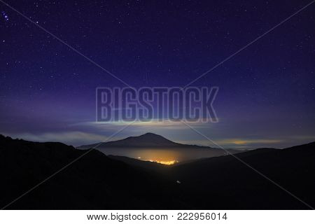 night light of Randazzo town glowing under Etna Mount and sky full of stars   from Nebrodi Park, Sicily