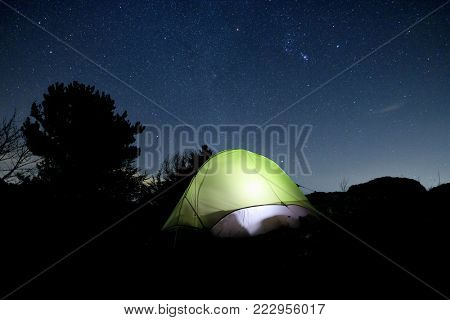 green tent glowing at night against sky full of stars in Nebrodi Park, Sicily