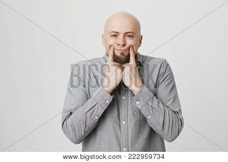 Caucasian handsome man with a fake smile stretching mouth using hands over white background. Bearded guy in casual clothes fed up of everything showing his tiredness of being around people.
