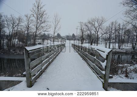 snow covered wooden pedestrian footbridge in winter over a creek stream