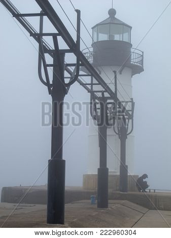 On rare warm days in winter dense fog may limit the view of the inner and outer lights of the Saint Joseph Lighthouse in Saint Joseph, Michigan. Though the end of the pier and Lake Michigan are just beyond the outer light, on this day one could see the li