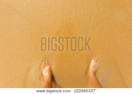 a man stands on the sand, men's feet on the sand. vacation concept with copy space