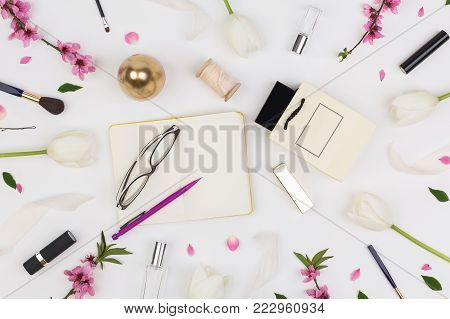 femininity, organisation, lifestyle concept. among white tulips and brunches of oriental cherry there are different cosmetics stuff and glasses with daily planner