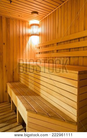 atmosphere, decor, relaxation concept. there is a corner of steam bath room with wooden benches that are made like stair, the room is illuminated with soft light