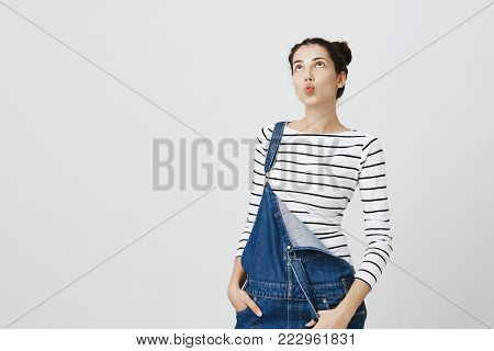 Pensive dreamy student girl posing against gray background, pouting lips, looks thoughtfully aside, hold hands in pockets of denim overalls. Cute young woman thinking about her tonight plans. Horizontal shot.