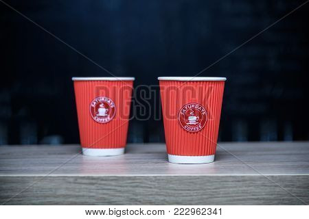 Lviv, Ukraine - January 21, 2018: The Saturdays coffee cafe, two one-time paper cups for coffee on bar counter, place where you can drink delicious coffee