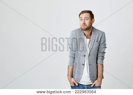 Portrait of puzzled bearded european male wears fashionable clothes, keeps hands in pockets, raises eyebrows in bewilderment, shrugs shoulders, has to make difficult life choice, lookes confused