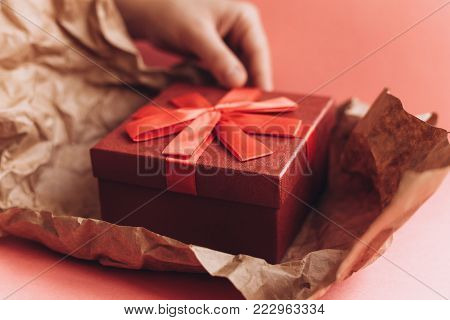 The girl has received a gift in a beautiful red box with a ribbon and is going to open it. Happy event.