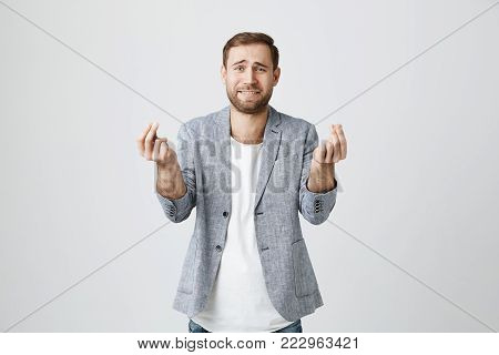Attractive good-looking male with beard gestures actively, hopes for fortune during special event or occasion, asks for something, isolated against gray background. People, face expressions, and body language concept
