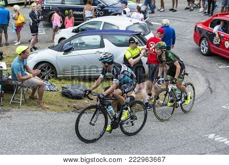 Col du Glandon, France - July 24, 2015: Three cyclists (Uran of Etixx-Quick-Step and Gautier of Europcar),climbing the road to Col du Glandon in Alps, during the stage 19 of Le Tour de France 2015.