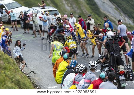 Col du Glandon, France - July 24, 2015: Excited spectators cheering the Yellow Jersey (Froome) while climbing the road to Col du Glandon in Alps, during the stage 19 of Le Tour de France 2015. Selective focus on the broadcaster on the motorbike.