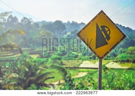 Yellow road sign warning of steep gradient of roads in Sumatran rural countryside, Indonesia