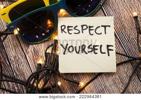 Respect Yourself on Sticky note paper with sunglasses, wooden background with lights