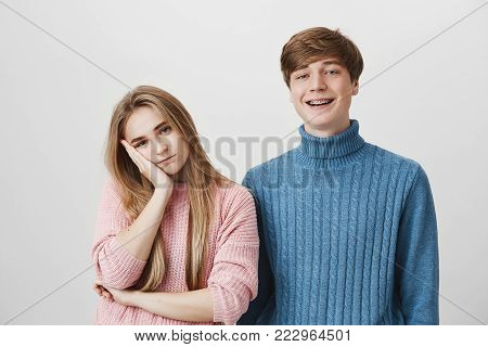 Family and relationships concept. Studio shot of irritated blonde girl resting her head on hand, because she is tired of her younger brother s jokes and behaviour. Body language and face expression.