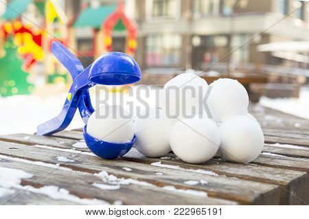 Blue plastic snowball maker tool with set of ready snowballs laying on a wooden bench near outdoor children playground at winter day.