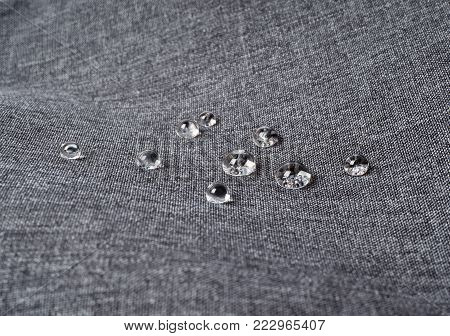 Gray waterproof fabric with waterdrops close up
