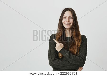Pretty smiling joyfully female with dark hair, pointing her index finger, showing copy space for advertising content. Studio shot of good-looking beautiful girl isolated against studio wall.