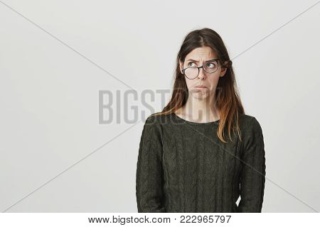 Waist-up portrait of unsatisfied thinking caucasian female model with long brown hair, looking away with awry glasses, isolated over white background. Young student makes first steps in science. Copy space