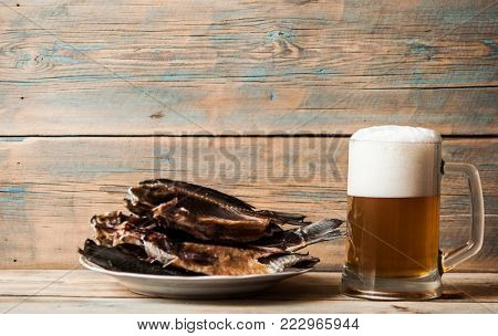 dried fish and vintage glass of beer on wooden background